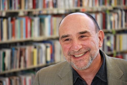 Fotografia di Philip Schultz che sorride; sullo sfondo scaffali con libri.