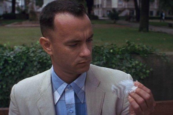L'attore Tom Hanks, nel ruolo di Forrest Gump, osserva una piuma d'uccello.