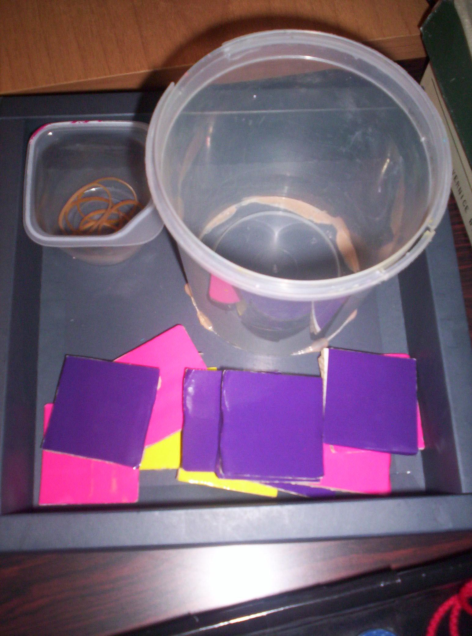 Una piccola scatola contenente alcuni elastici. Un contenitore più grande e vuoto. Alcuni cartoncini quadrati rosa, gialli e viola.