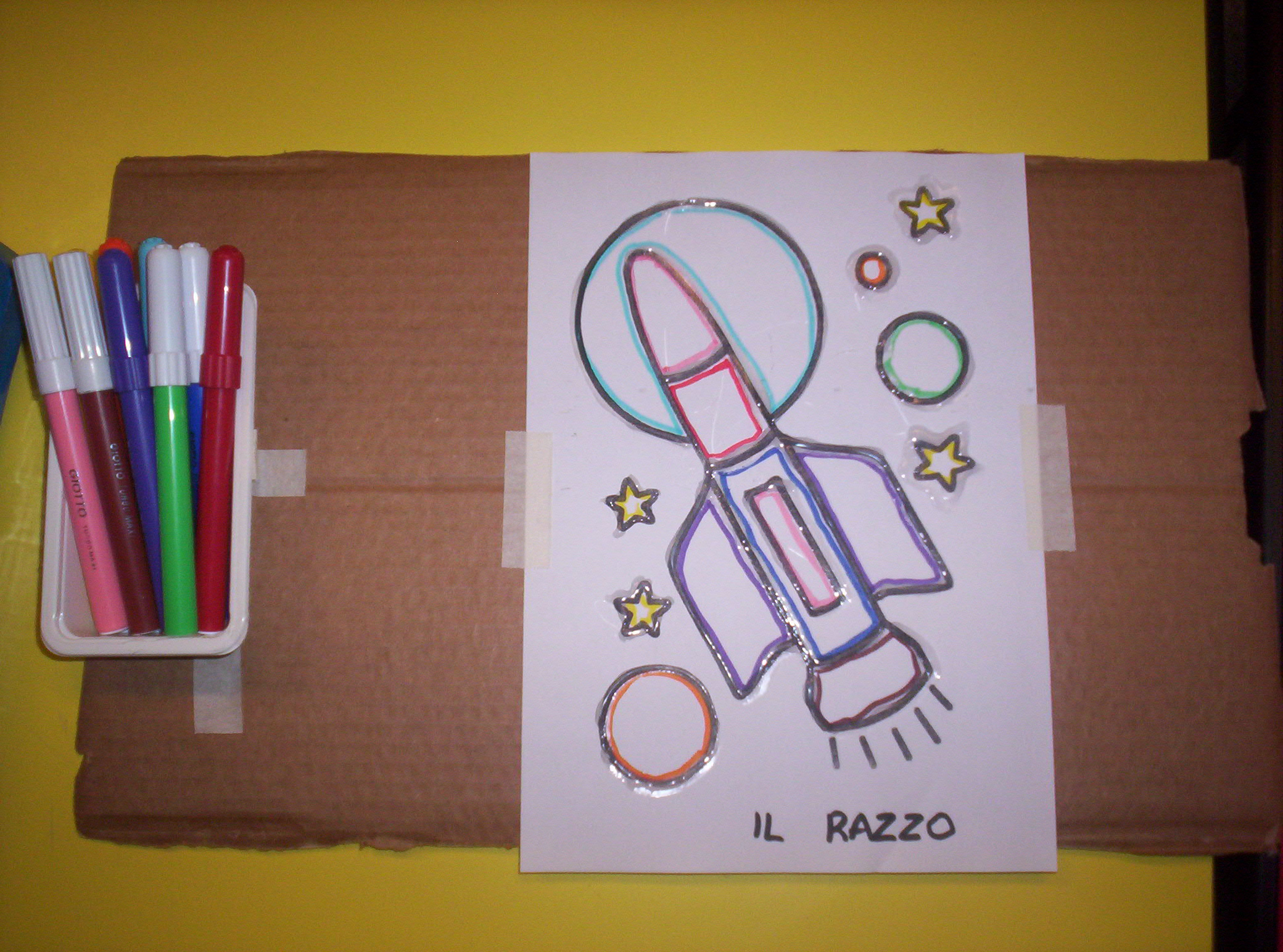 Su un cartone ci sono: a sinistra una vaschetta con dei pennarelli grossi e a destra il disegno di un razzo con contorni colorati ripassati con colla a caldo.