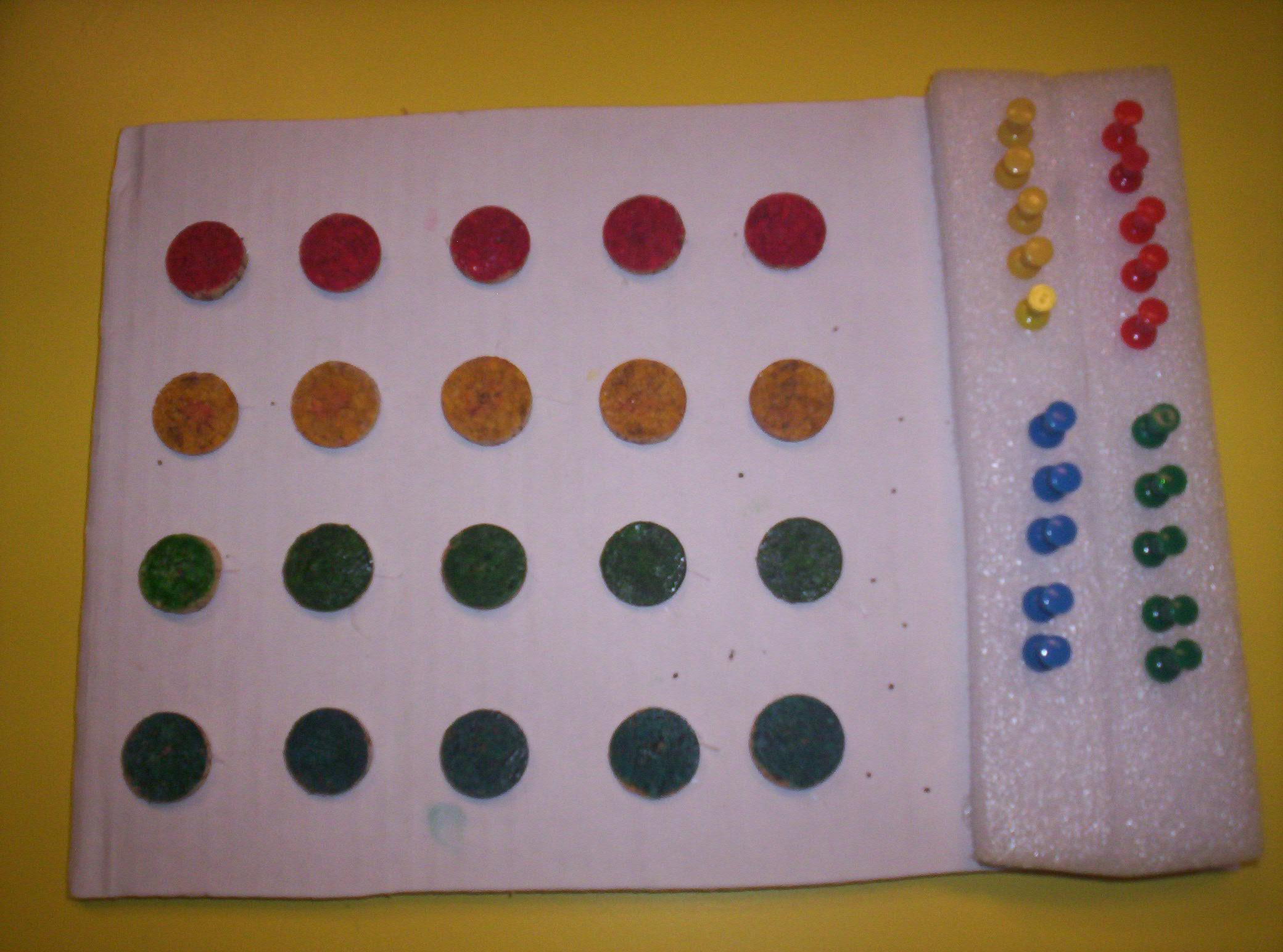 Sulla sinistra quattro file con cinque bollini per ciascuna di colore rosso, verde, giallo e blu. Sulla destra due colonne di puntine gialle, rosse blu e verdi.