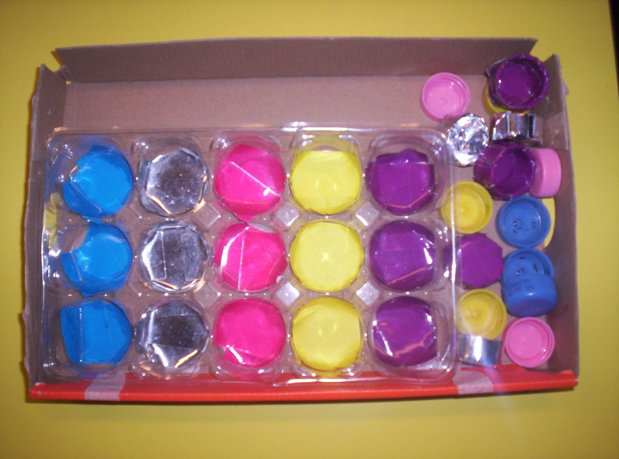 Scatola che contiene una vaschetta di plastica divisa in scomparti colorati e tappi colorati.