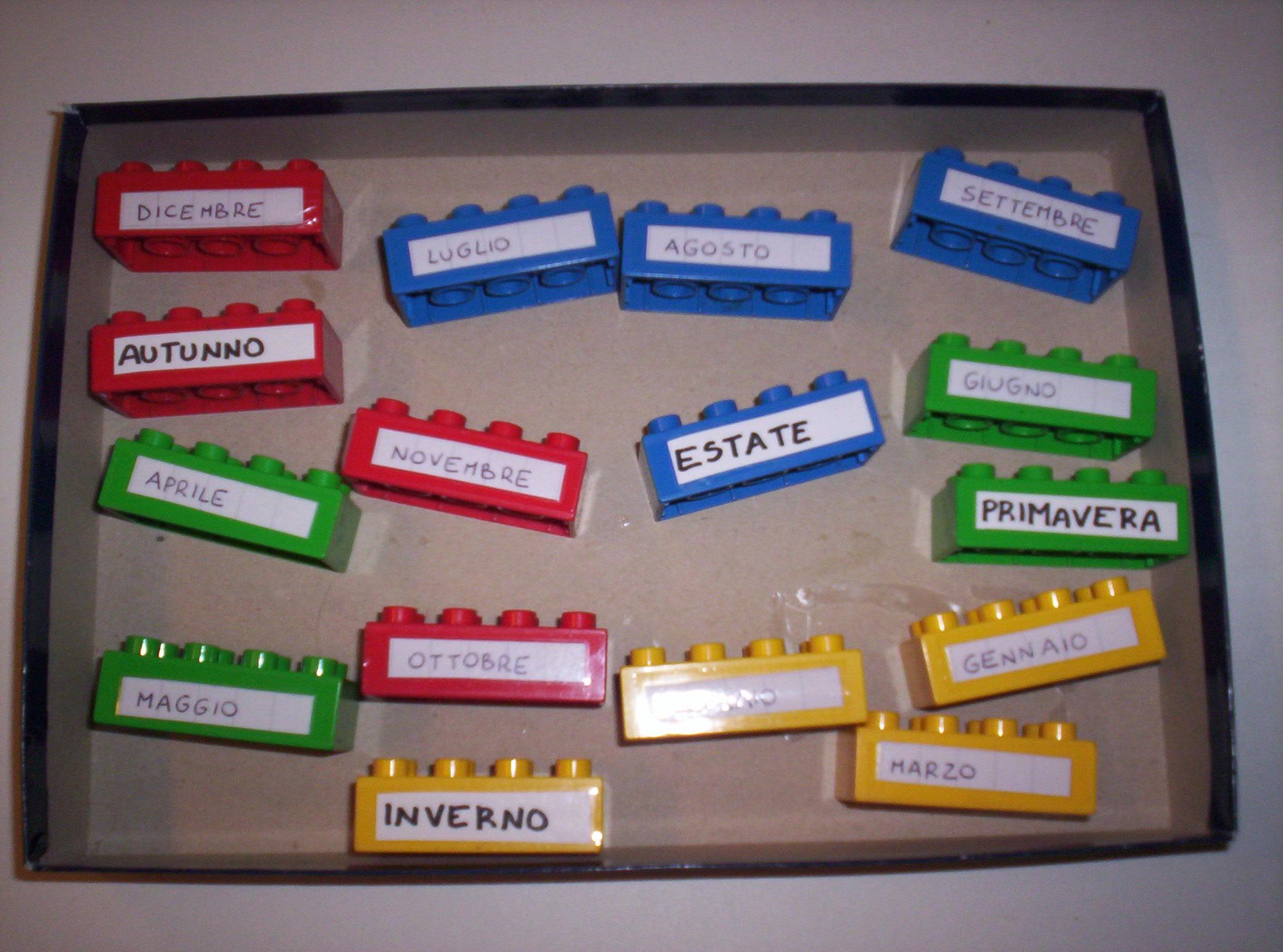 Una scatola contenete pezzi Lego colorati con scritti i nomi dei mesi e delle stagioni.