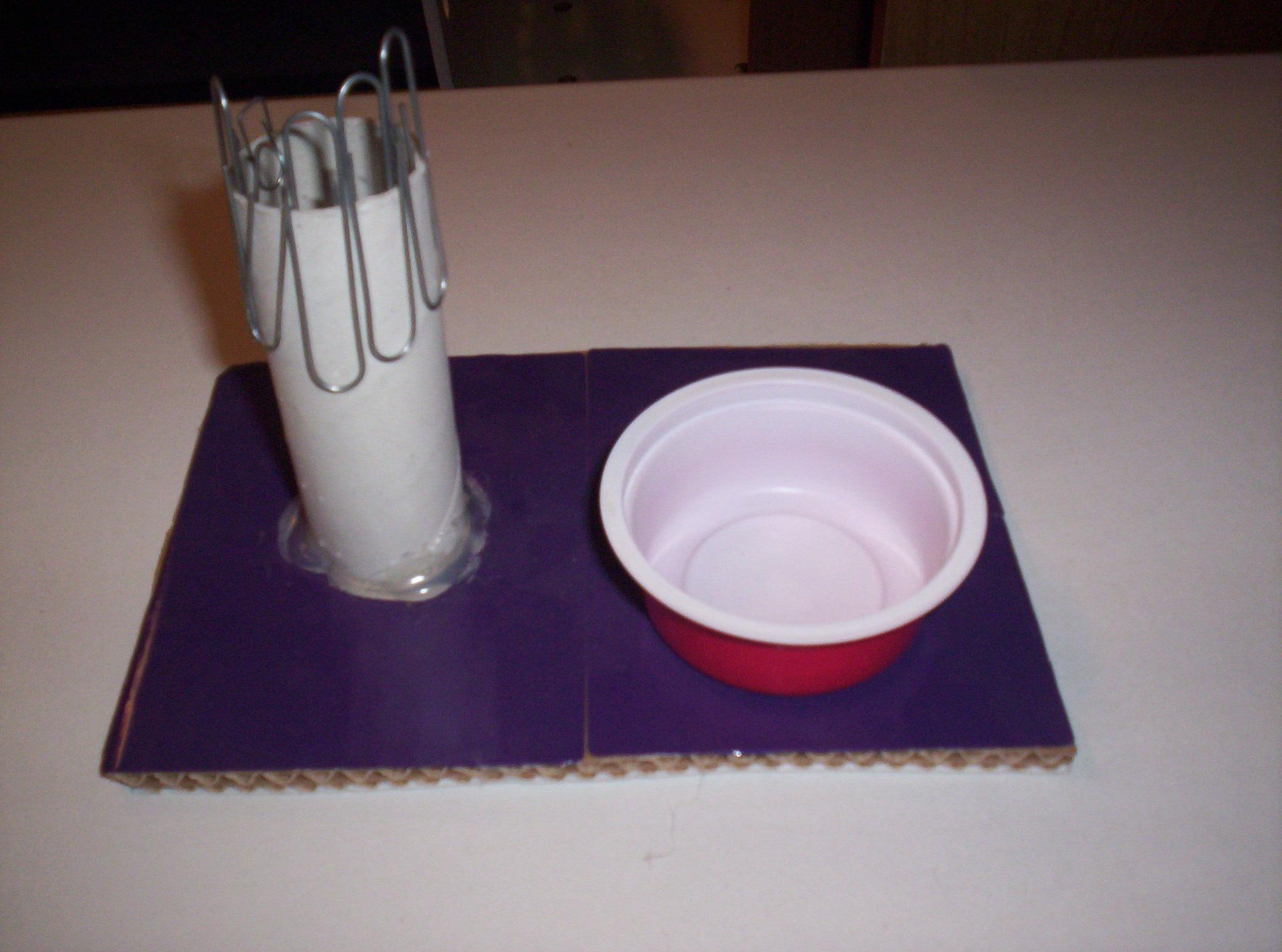 Su un pezzo di cartone sono incollati a sinistra un cilindro di cartone con infilate alcune graffette e a destra un piccolo contenitore in plastica rossa.