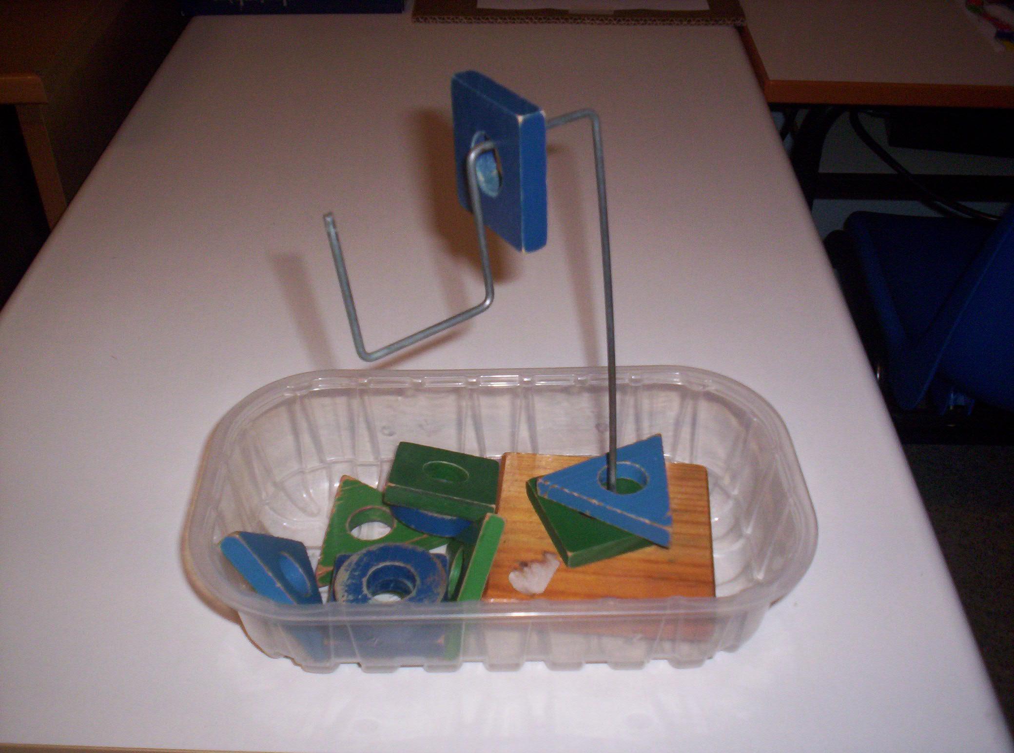 Vaschetta trasparente con forme di legno con un foro centrale e un ferro a forma di esse rovesciata con infilato un quadrato blu.