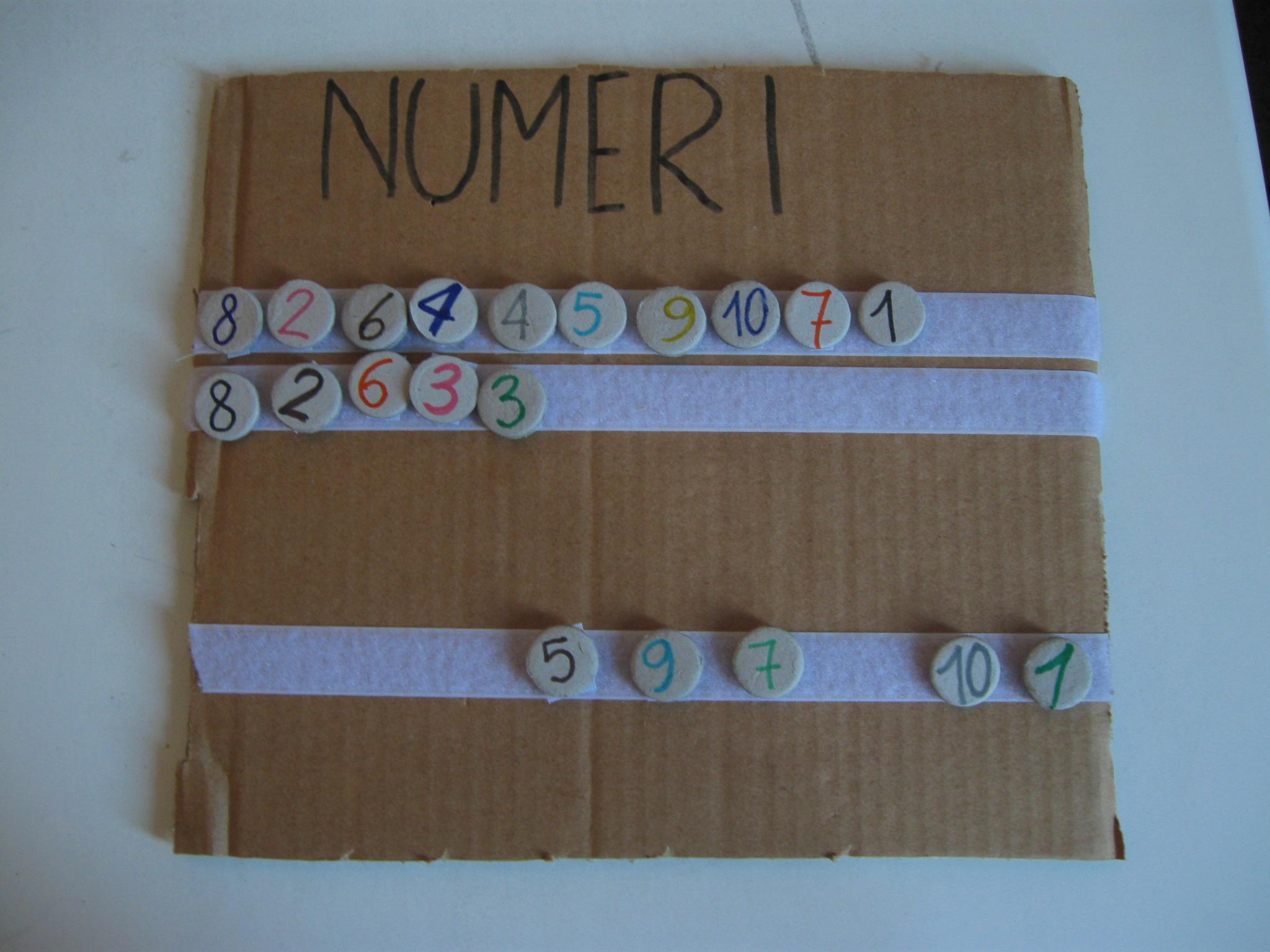 Cartoncino con attaccate tre strisce di velcro sovrapposte: sulla prima c'è una sequenza di numeri, sulla seconda parte della sequenza e sulla terza numeri in disordine.
