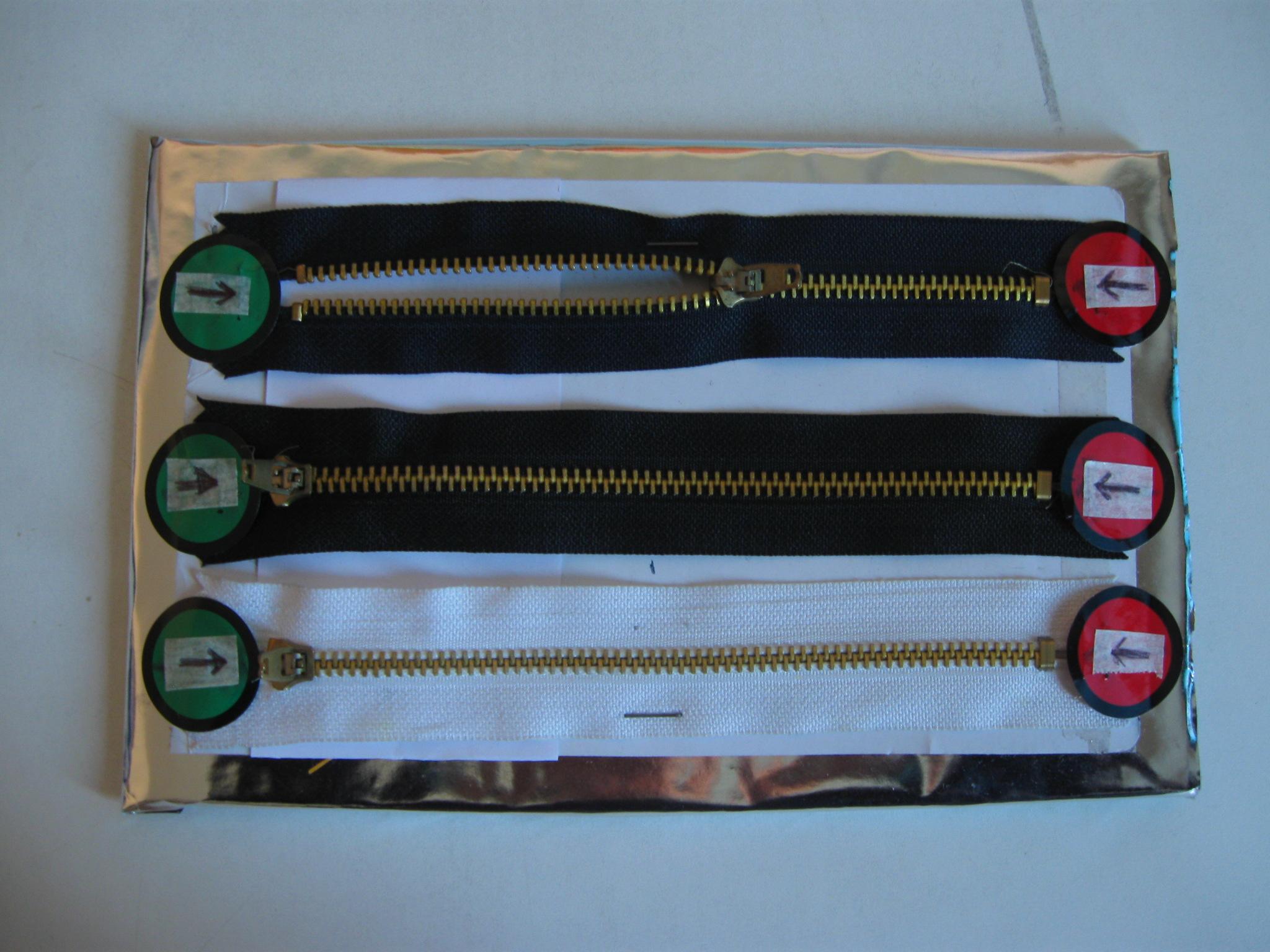 Tre cerniere con un bollino verde all'inizio e uno rosso alla fine. Due sono chiuse e una è aperta fino a metà.