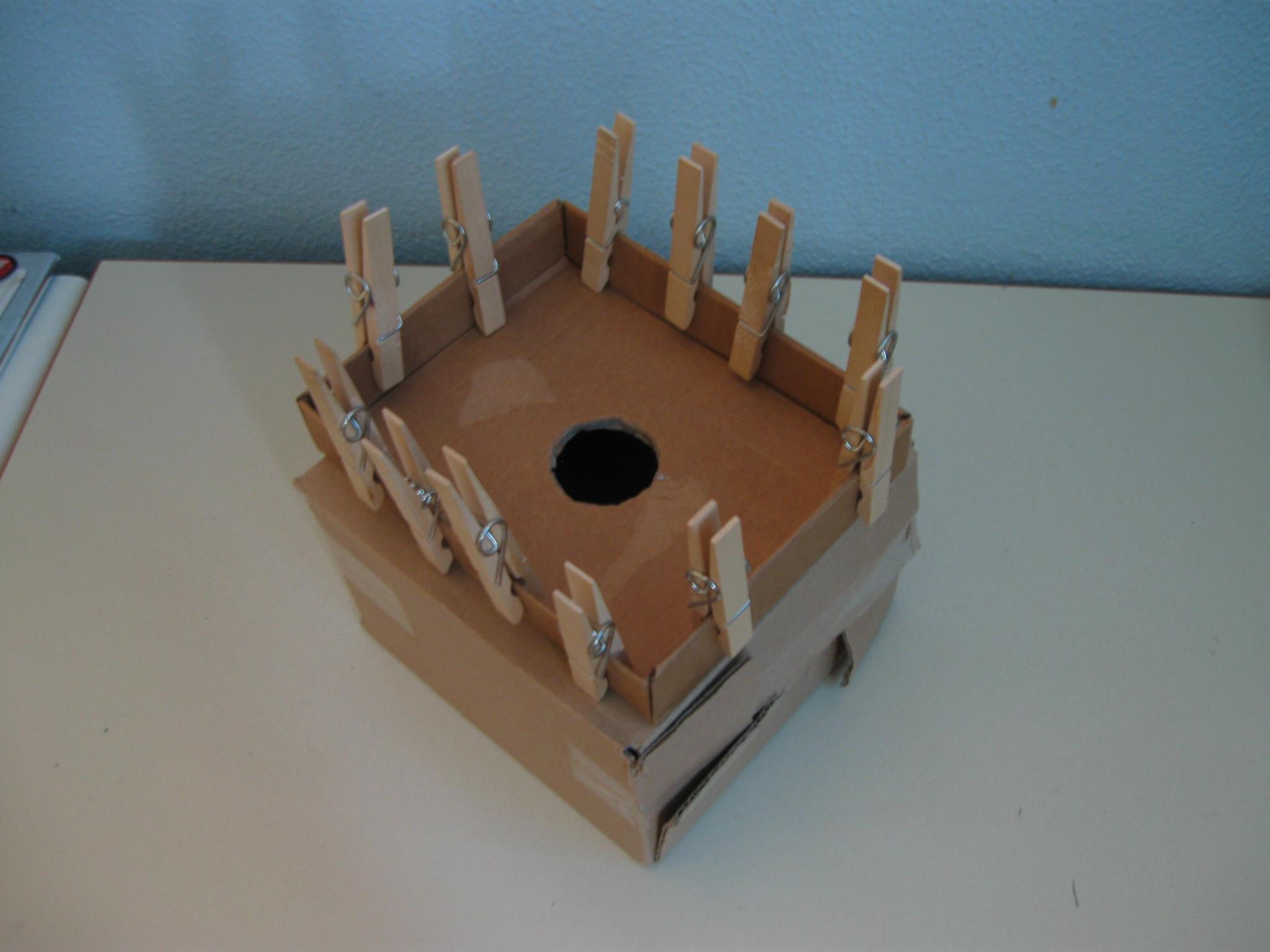 Una scatola quadrata con appese dodici mollette e al centro un foro.