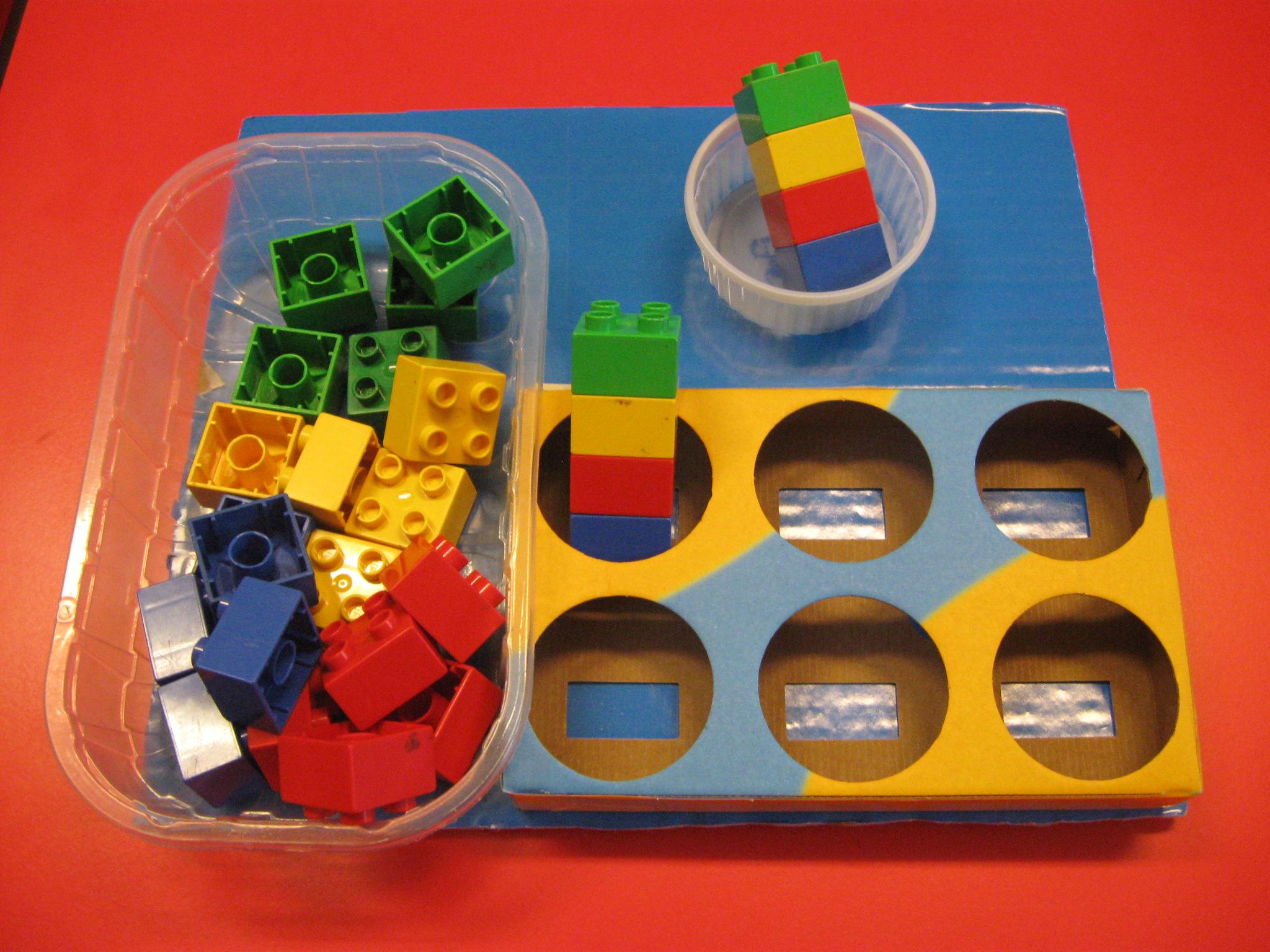 A sinistra una vaschetta di plastica contenenete pezzi di Lego duplo quadrati di colore giallo, rosso, blu e verde. A destra quattro cubetti impilati messi in un contenitore rotondo e sotto una vaschetta di cartone divisa in sei spazi, nel primo ci sono quattro cubetti impilati.