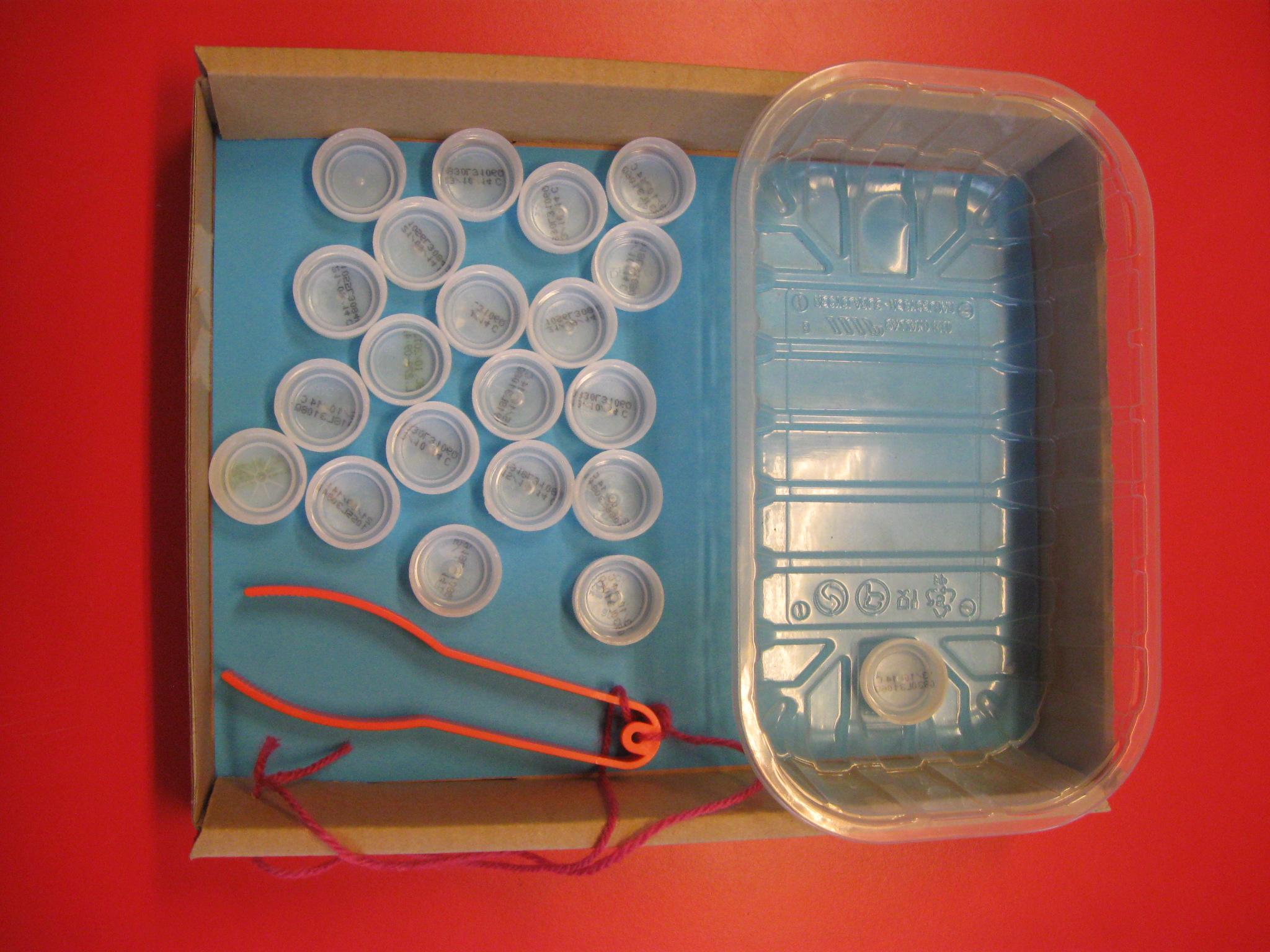 In una scatola ci sono una vaschetta in plastica, tappi di bottiglia e una pinza in plastica.