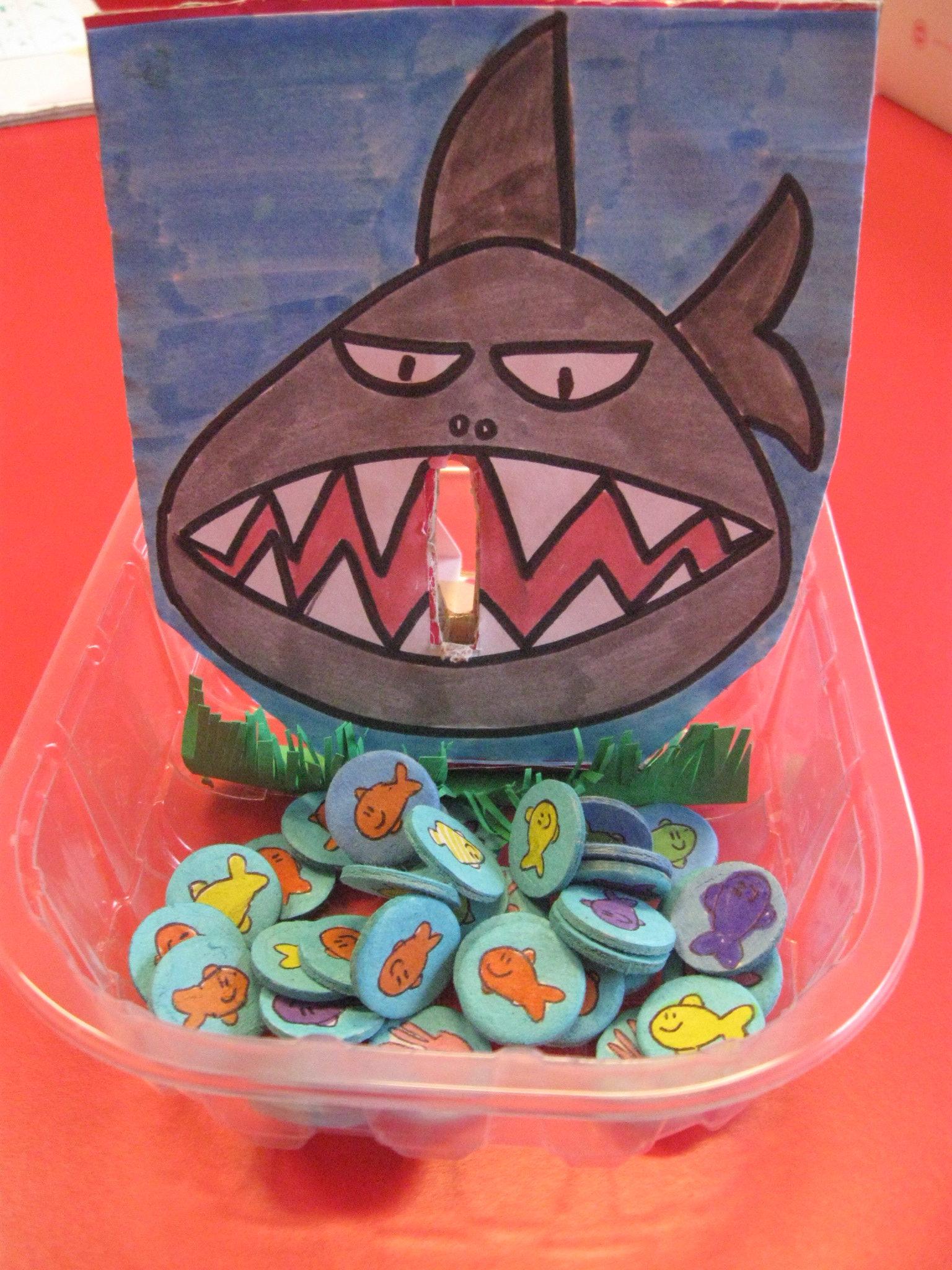 Uno squalo con una grande bocca con una fessura disegnato su un cartoncino. Gettoni con disegnati dei pesciolini.