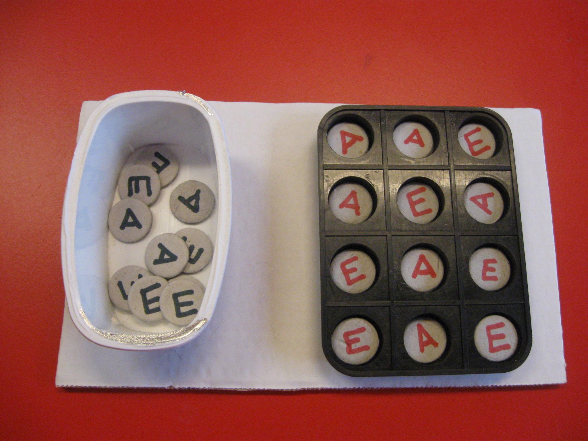 Contenitore suddiviso in spazi contenenti la vocale A e la vocale E scritte in rosso. Di fianco un contenitore con le vocali A ed E scritte in nero.