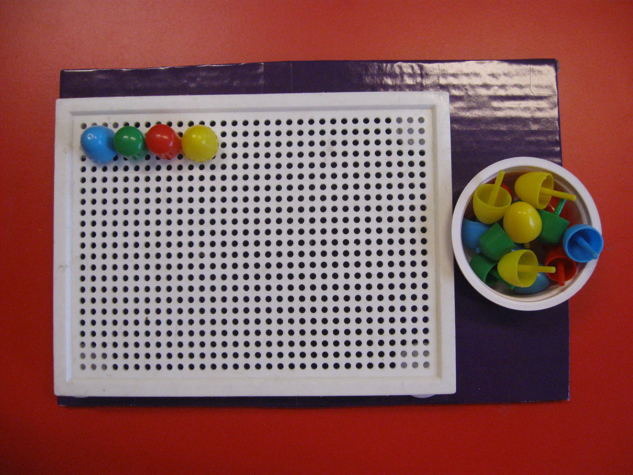 Sulla sinistra una tavoletta di plastica per chiodini con infilati quattro chiiodini. sulla destra una ciotola con chiodini colorati.