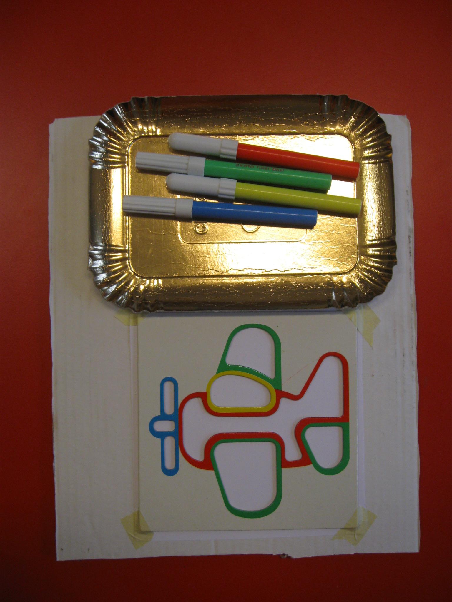 Cartone su cui sono posati un contenitore con pennarelli e uno stencil di un aereo adagiato su un foglio.
