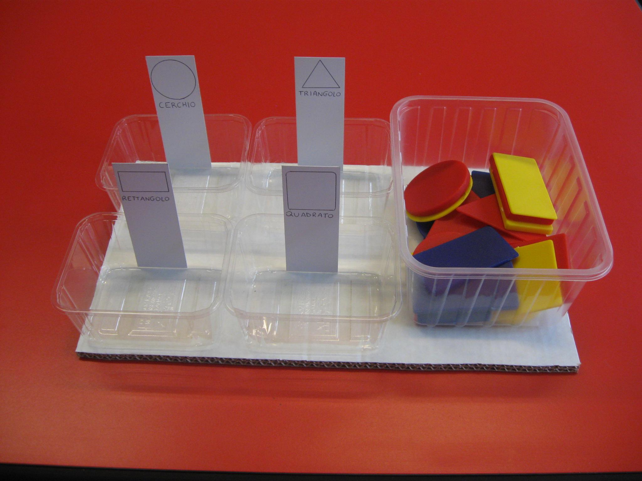 Sulla sinistra quattro vaschette con un cartoncino ciascuna che riproduce una forma geometrica. Sulla destra un contenitore contenente diverse forme geometriche di plastica.