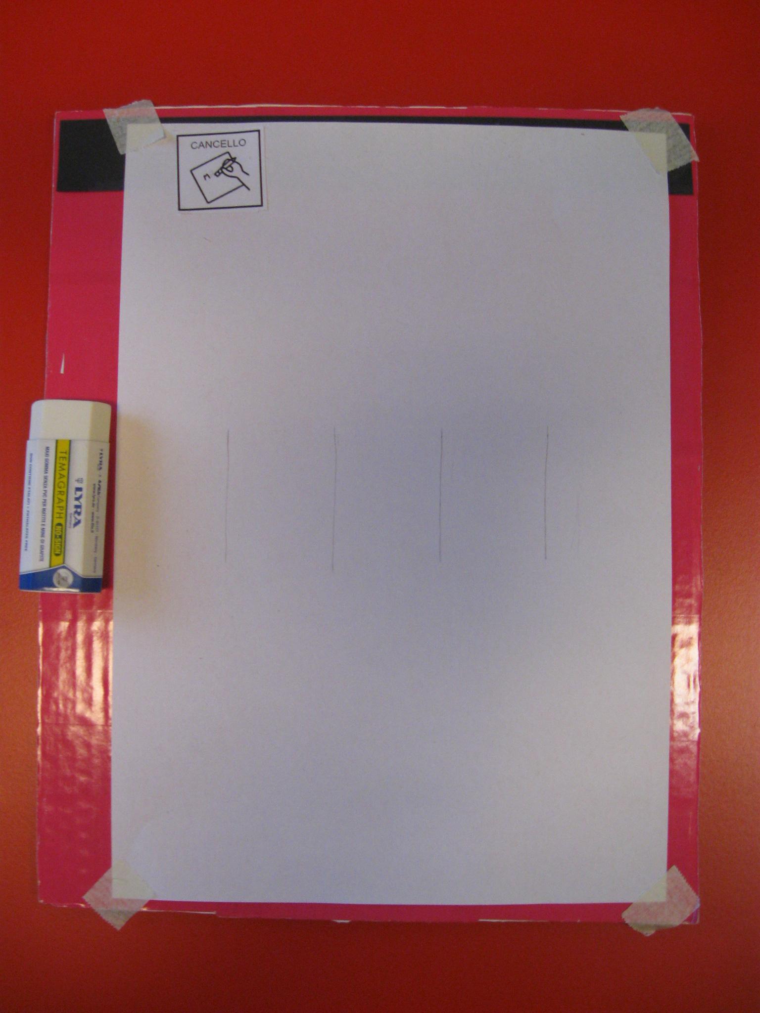 Su un cartone è fissato un foglio con disegnate quattro linee verticali in matita. A sinistra del foglio è posizionata una gomma.