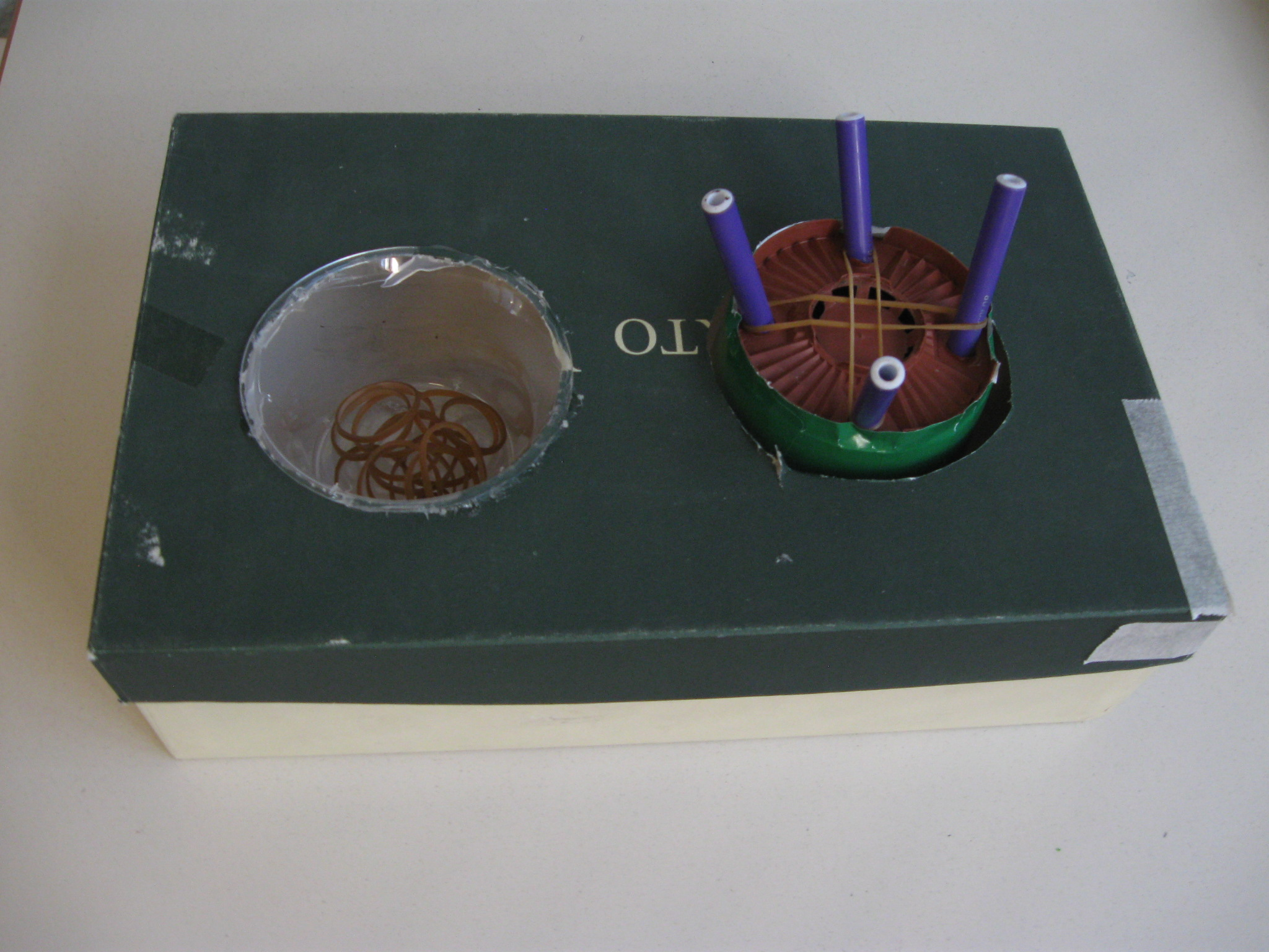 Due picoole scatole, una contenente alcuni elastici, l'altra con incastrati verticalmente quattro pennarelli sui quali sono infilati due perpendicolarmente due elastici.