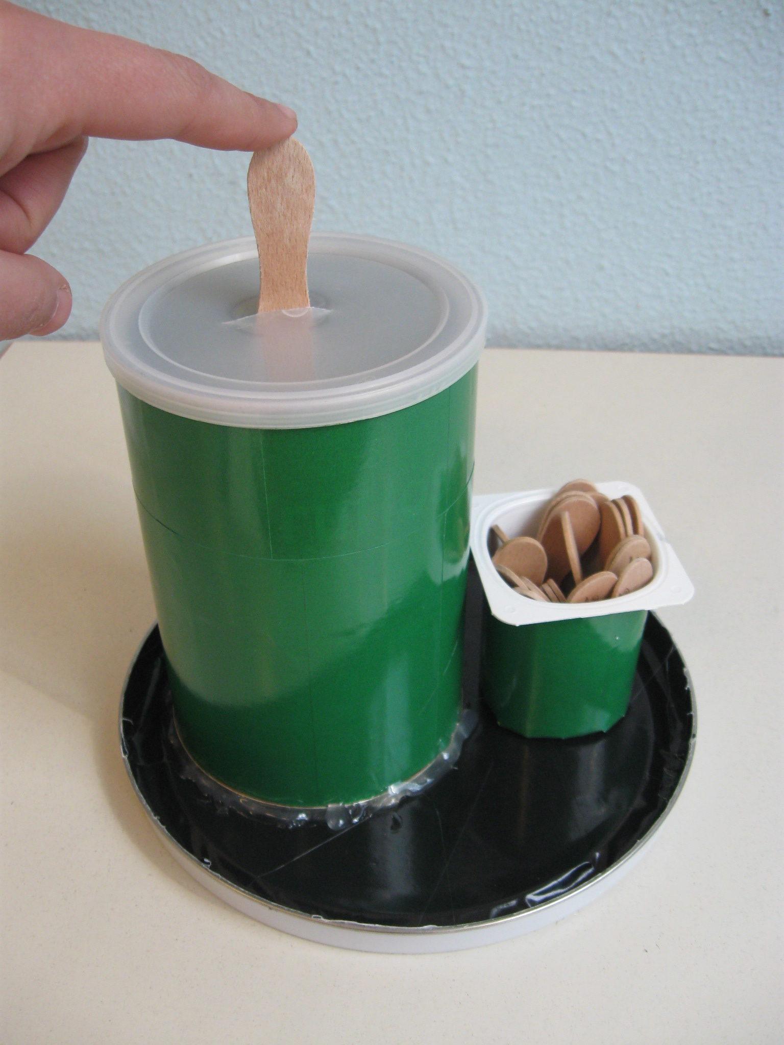 Una mano inserisce dei bastoncini da gelato nel foro del coperchio di un barattolo.