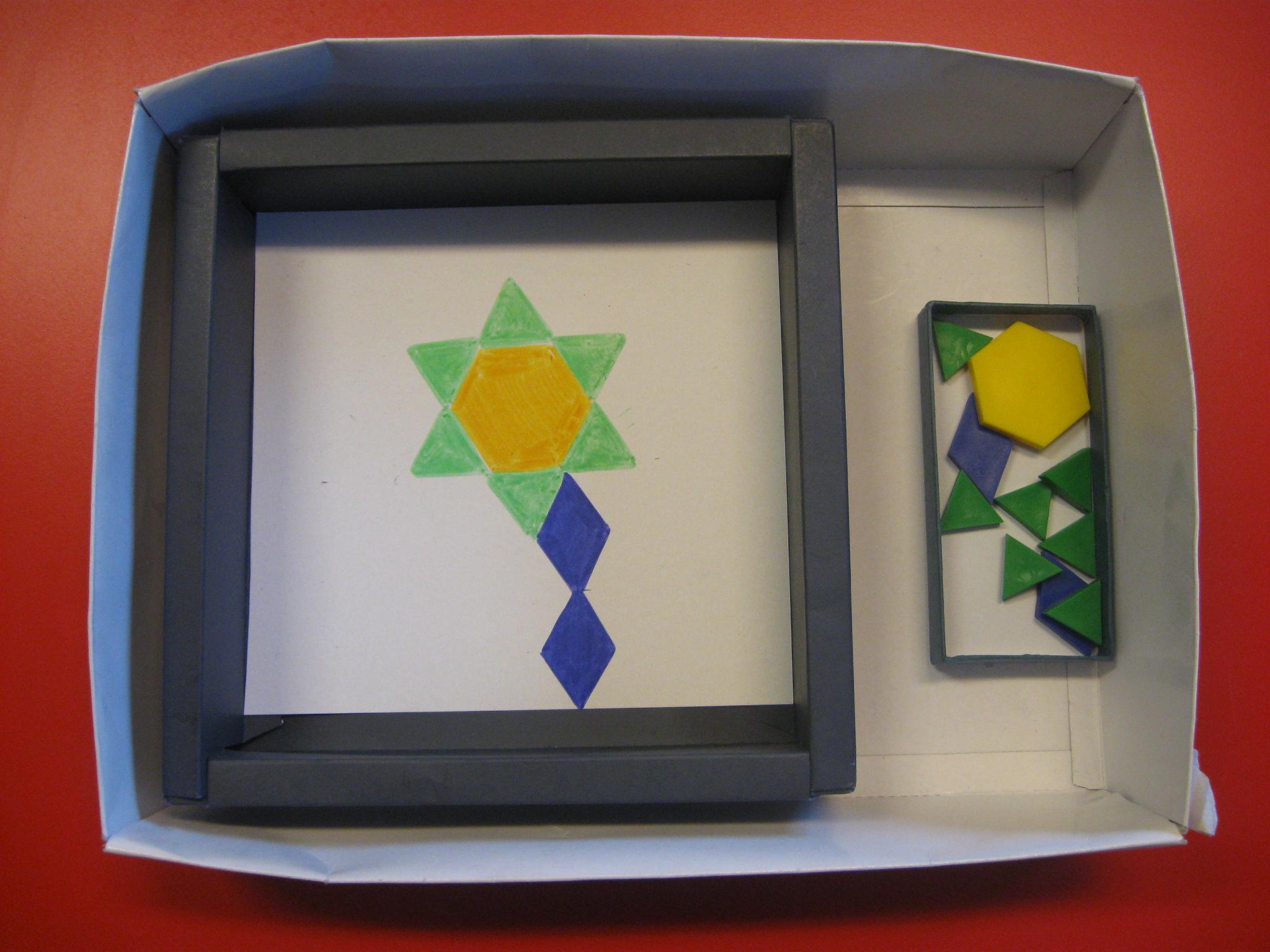 Una scatola contenente un fiore disegnato. Una scatoletta contenente forme di plastica colorata.