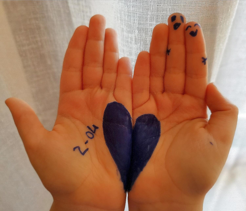 Mani con cuore blu e data 2 aprile